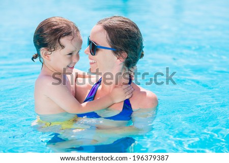 Portrait of woman holding her little son while standing in the pool - stock photo