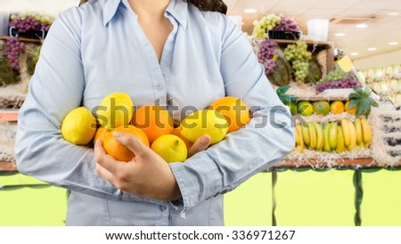 portrait of woman holding in her arms citric fruits like lemons and oranges at the greengrocer on the background - stock photo