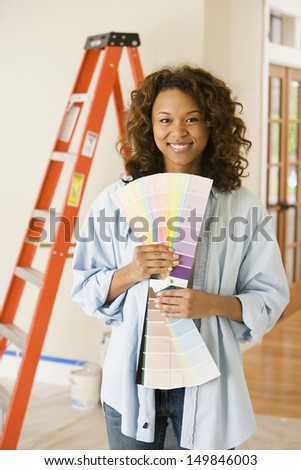 Portrait of woman holding paint swatches - stock photo