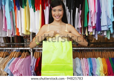 Portrait of woman in clothing store holding bag - stock photo