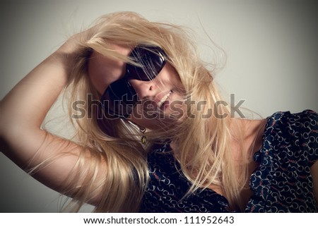 Portrait of woman in dark glasses with hair fluttering from a wind - stock photo