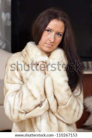 Portrait of woman  in fur coat  at home interior - stock photo