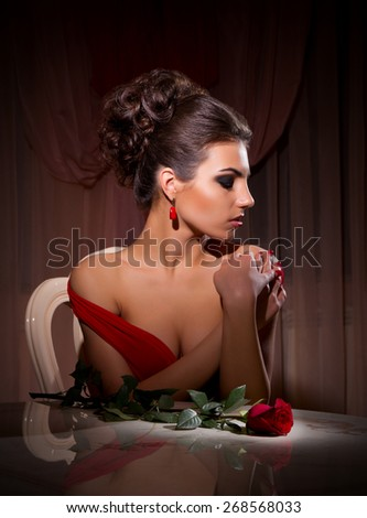 Portrait of woman in red dress with rose flower - stock photo