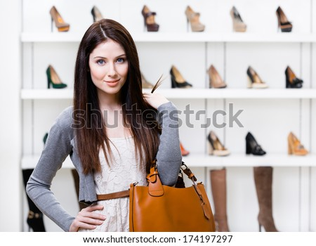 Portrait of woman in shopping center in the section of female footwear. Concept of consumerism and stylish purchase - stock photo