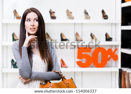 Portrait of woman in shopping center with 50% sale in the section of female high heeled shoes. Concept of consumerism and stylish purchase - stock photo
