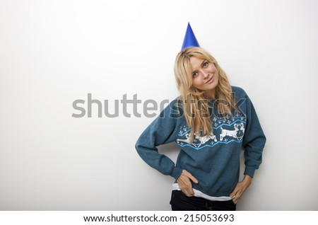 Portrait of woman in sweater wearing party hat against white background - stock photo