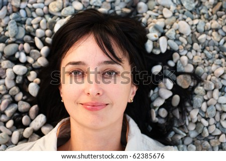 Portrait of woman lie on the stone beach - stock photo