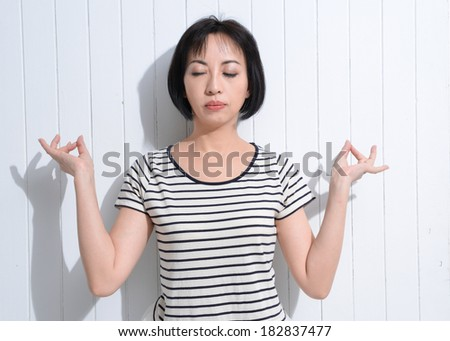 Portrait of woman meditating in pose of lotus in isolation. Casual clothes. - stock photo