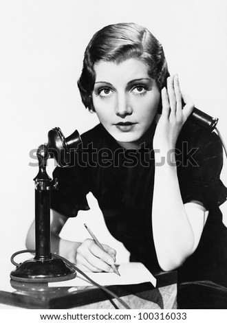 Portrait of woman on telephone taking notes - stock photo