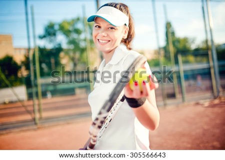 Portrait of woman playing tennis, holding racket and ball. Attractive brunette girl wearing white t-shirt and cap on tennis court - stock photo