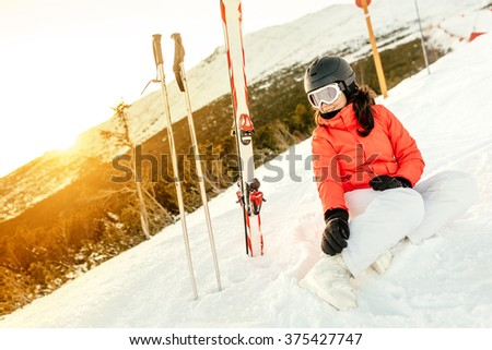 Portrait of woman sitting on snow, enjoying the view from mountains - stock photo