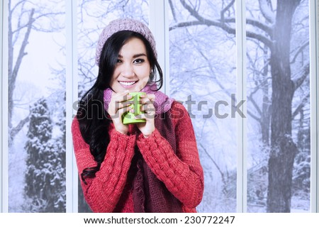 Portrait of woman smiling on the camera while enjoy a warm drink and wearing a knitted clothes at home - stock photo
