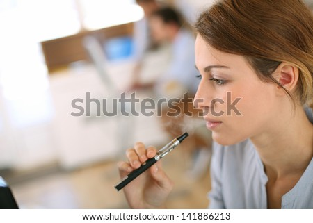 Portrait of woman smoking with electronic cigarette - stock photo
