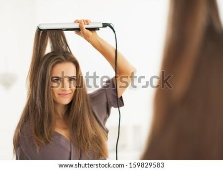 Portrait of woman straightening hair with straightener - stock photo