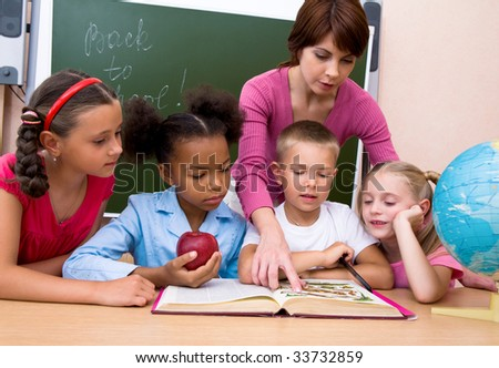 Portrait of woman teaching children and pointing to the book - stock photo