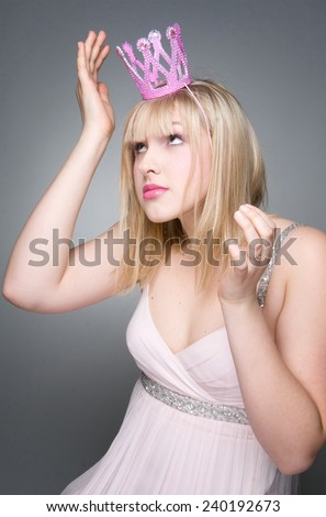 portrait of woman wearing pink princess crown - stock photo