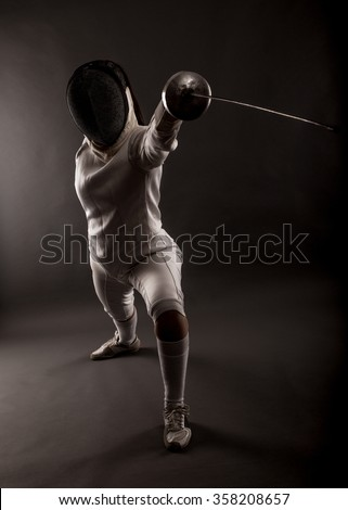 Portrait of woman wearing white fencing costume practicing with the sword. - stock photo