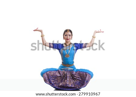 Portrait of woman with arms raised performing Bharatanatyam isolated over white background - stock photo