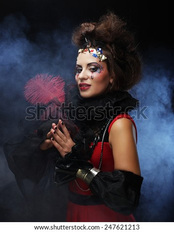 portrait of woman with artistic make-up in blue smoke, party theme - stock photo