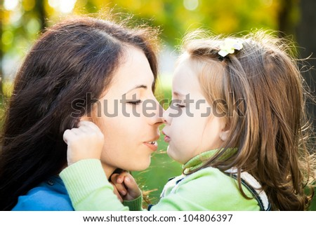 Portrait of woman with baby girl in autumn - stock photo
