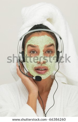 Portrait of woman with beauty mask on face listening to headphones - stock photo