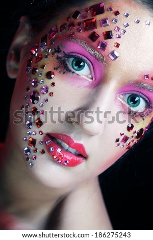 Portrait of woman with bright artistic make-up over smoke  background - stock photo
