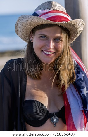 Portrait of woman with cowboy hat American flag - stock photo