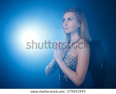 Portrait of woman with dark angel wings praying at the background of the blue light - stock photo