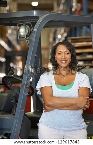 Portrait Of Woman With Fork Lift Truck In Warehouse - stock photo