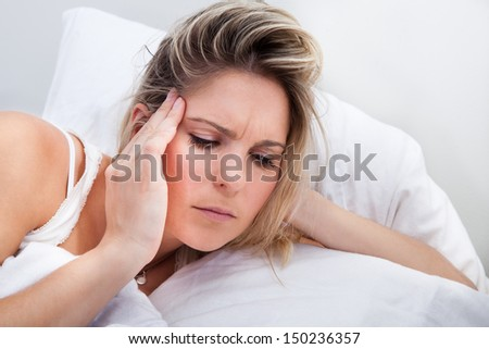 Portrait of woman with headache lying on bed - stock photo