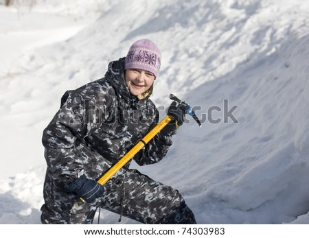portrait of woman with ice axe in snow - stock photo