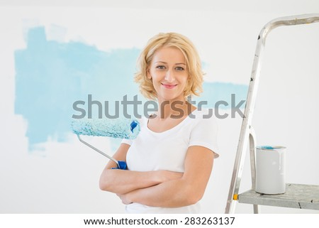 Portrait of woman with paint roller in new house - stock photo