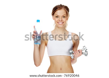 Portrait of woman with smile holding bottle of water and dumbbells - stock photo
