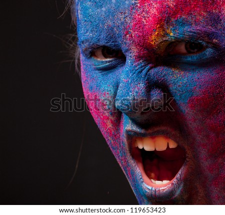 Portrait of woman with unusual paint make-up on black background - stock photo