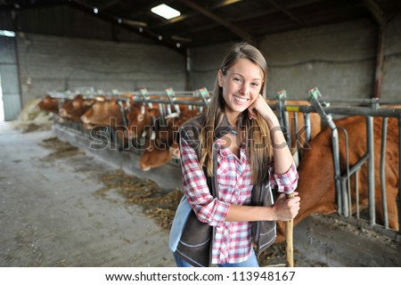 Portrait of woman working in barn - stock photo