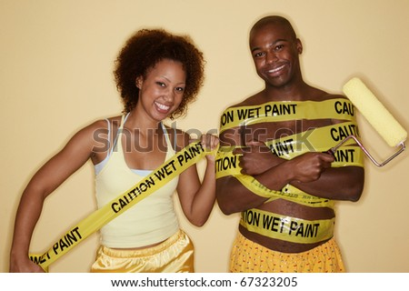 Portrait of woman wrapping man in caution tape - stock photo