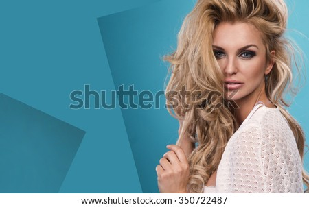 Portrait of wonderful young blonde woman with long hair looking at camera on blue background, smiling.  - stock photo