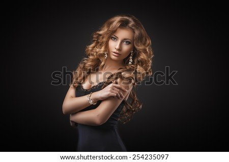 Portrait of wonderful young blonde woman with long hair looking at camera. Sexy girl in blue dress. Jewelry. Hairstyle. Glamour makeup. Vogue. Curly hair. - stock photo