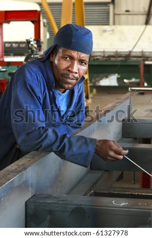 Portrait of worker in workshop looking at camera - stock photo