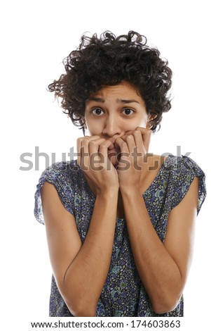 portrait of worried and stressed hispanic girl biting nails and looking at camera on white background  - stock photo