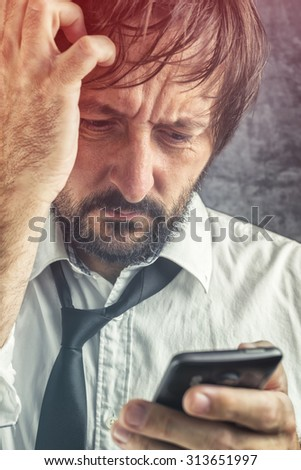 Portrait of worried businessman received bad news via SMS message or e-mail on mobile smart phone, selective focus on face - stock photo