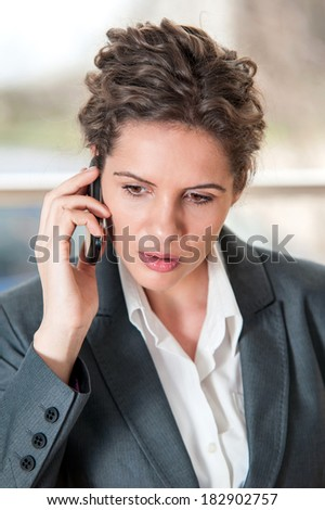 Portrait of worried businesswoman talking on the phone - stock photo