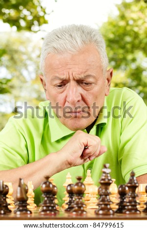 Portrait of worried elderly man playing chess outdoors. - stock photo