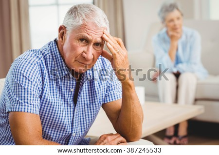 Portrait of worried senior man sitting on sofa in living room - stock photo
