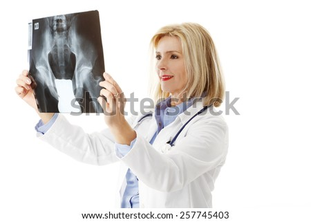 Portrait of x-ray specialist analyzing x-ray image while standing against white background.  - stock photo