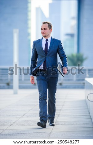 Portrait of yang businessman in suit outdoors.Walking man. - stock photo