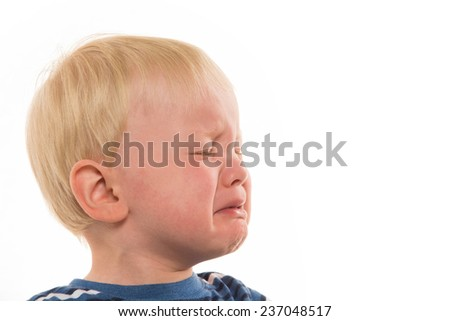 Portrait of 2-year-old blond boy crying with striped shirt on white background - stock photo