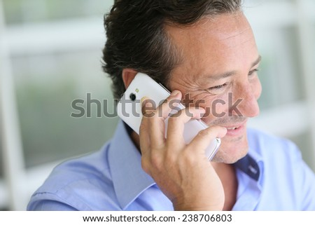Portrait of 40-year-old man talking on cellphone - stock photo