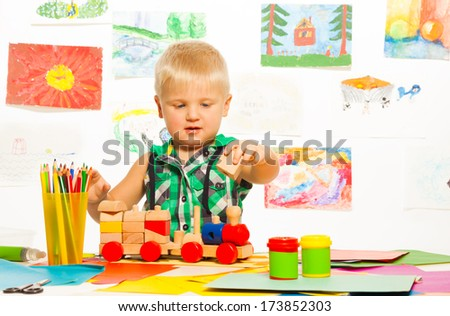 Portrait of 2 years old blond boy in the preschool art class  with pencils toys and blocks - stock photo
