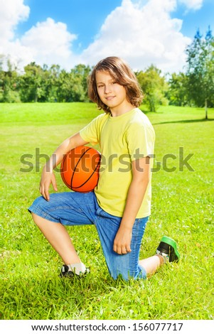 Portrait of 12 years old boy sit on squads with basketball ball on the field on bright sunny day - stock photo